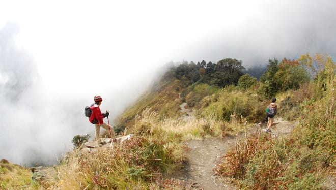 Clouds waft across the trail along a ridge above the village of Ghorepani, in central Nepal. Some travelers hire a porter to help carry gear and allow trekkers to travel with smaller knapsacks.