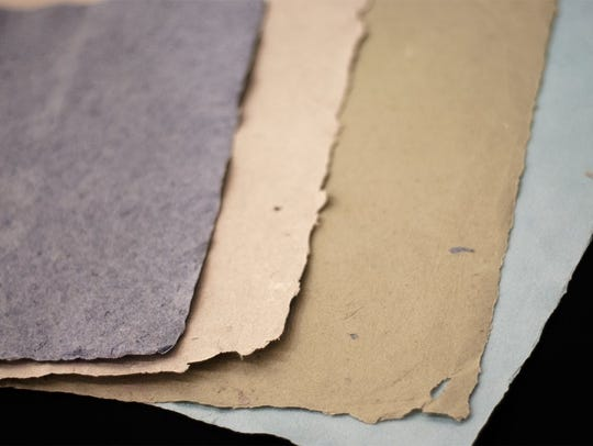 Examples of handmade paper from military uniforms.