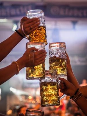 Oktoberfest attendees in Germany raise their beers in celebration of the event.