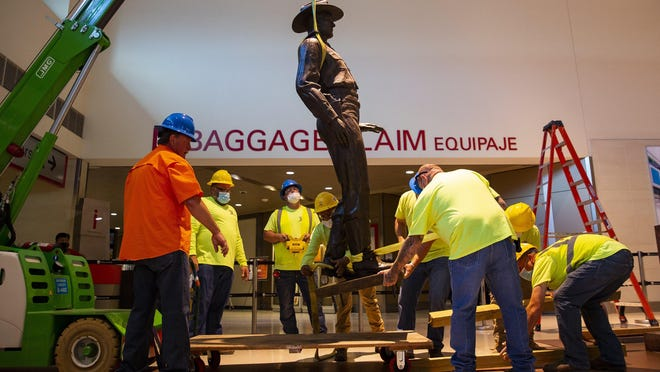 """A crew removes a 12-foot-tall bronze statue of a Texas Ranger, called """"One Riot, One Ranger,"""" from the main lobby inside Love Field airport on June 4."""