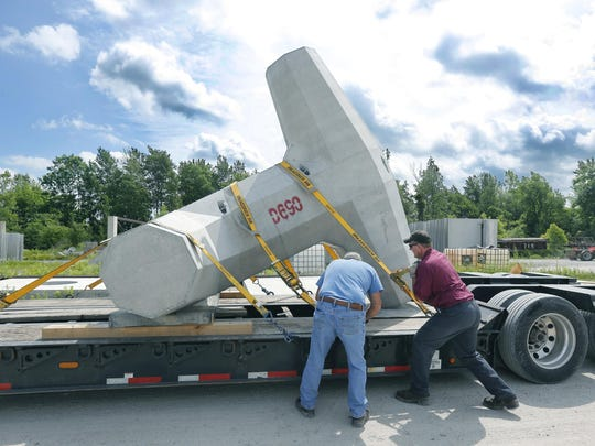 Truck drivers Dave Kurtz and Rich Minning, both with Jeff Coniber Trucking LLC, secure a 32,000-pound dolos to a truck.
