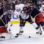 Columbus' Sergei Bobrovsky (72) makes a save as teammate Jack Johnson, right, tries to clear Pittsburgh's Lee Stempniak from in front of the net during the first period Monday.