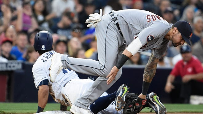 Tigers' Nicholas Castellanos dives for the throw as Padres' Chase d'Arnaud slides safely into third base during the third inning.