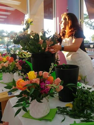 Melissa Beck distributes floral pieces during an Alice's Table event at the Tipsy Cow in Bonita Springs. The classes are available throughout Southwest Florida and Cape Coral.