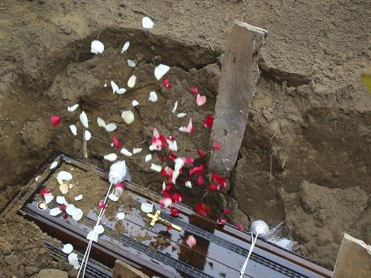 Relatives throw flower petals on the coffin of Dhami Brandy, 13, a victim of Easter Sunday's bomb blast at St. Sebastian Church, in Negombo, Sri Lanka Thursday, April 25, 2019.