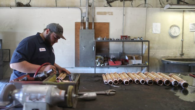 Global-Flex employee Saxon Zanni works with metal hose Wednesday April 25 at the business in Redding.