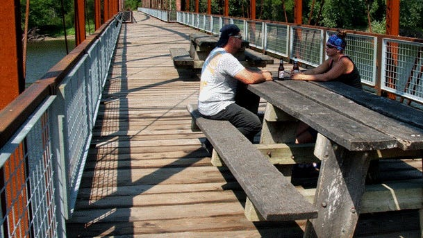 Cris and Jill Jaster of Walford relax Friday noon on Sutliff Bridge.