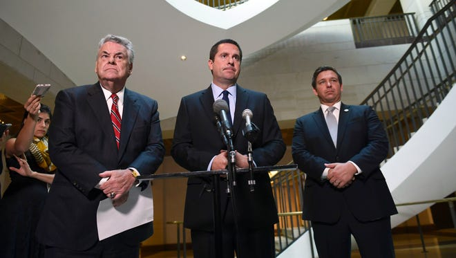 House Intelligence Chairman Devin Nunes, standing with Reps. Peter King and Ron DeSantis, listens to a reporter's question as he speaks on Capitol Hill on Oct. 24, 2017.