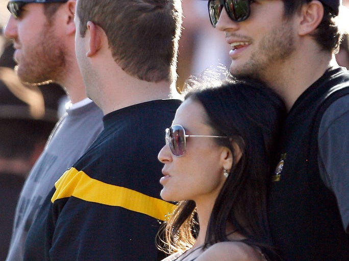 Actors Ashton Kutcher and Demi Moore watch from the sidelines during the fourth quarter, Saturday, Nov. 7, 2009, at Kinnick Stadium, in Iowa City, Iowa.