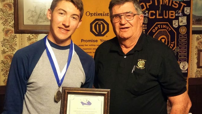 """David Velez, a sophomore at Deming High School, poses with Deming Optimist Club President Charles """"Tony"""" Sayre after receiving his award as an essay contest winner."""