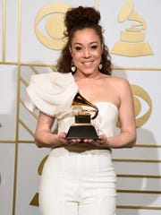 """Kendra Foster poses in the press room with the award for best R&B song for """"Really Love"""" at the 58th annual Grammy Awards at the Staples Center on Monday, Feb. 15, 2016."""