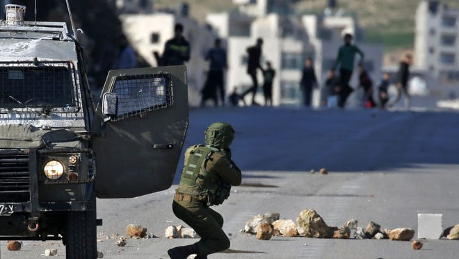 An Israeli soldier clashes with Palestinian protesters in the West Bank on Feb. 2, 2017.