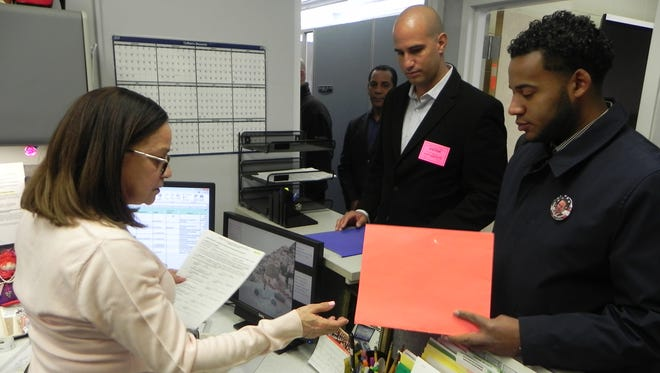 Omar Ledesma, at right, and Amicar Lopez deliver their completed ballot petitions for the upcoming Board of Education election to Adelina Rivera, left, at the school district business administrator's office.