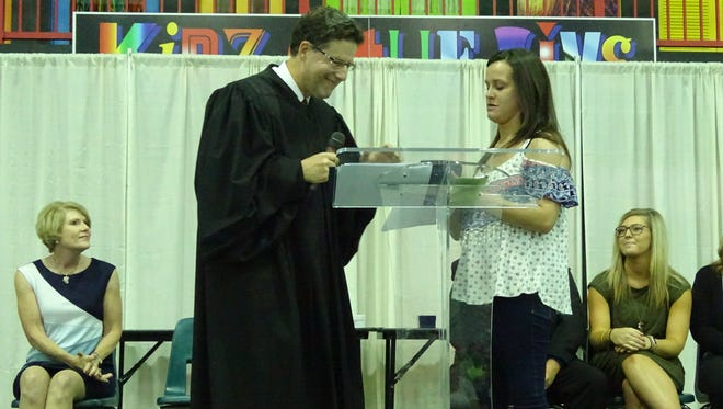 Marion County Judge Jim Slagle gives Tiffany White a certificate and gift card for graduating from drug court.