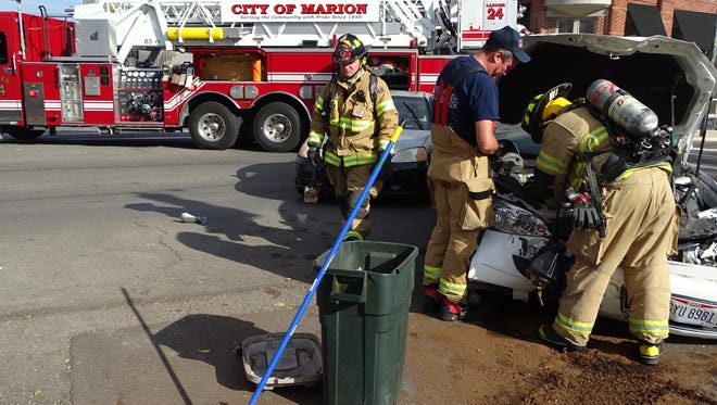 Marion City Fire Department was called to Center and State streets for a car crash that snarled downtown traffic  Tuesday. Firefighters scattered an absorbent material on the pavement to soak up oil and other fluids that spilled from one of the crashed cars.