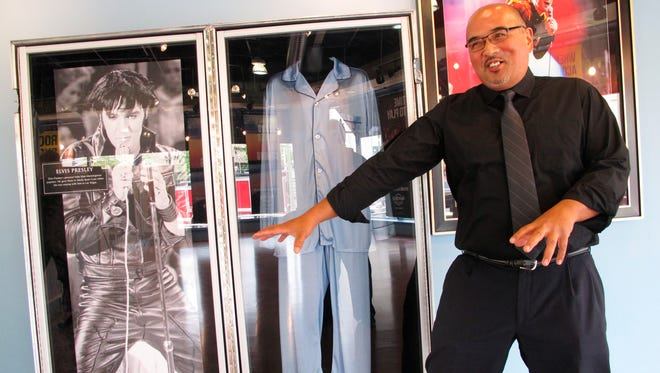 Alfred Kare, a waiter at the former Trump Taj Mahal Casino in Atlantic City, N.J. does his Elvis Presley impersonation near a pair of the singer's pajamas that will be on display at the Hard Rock casino. Kare will work as a waiter at the casino reopens this month.