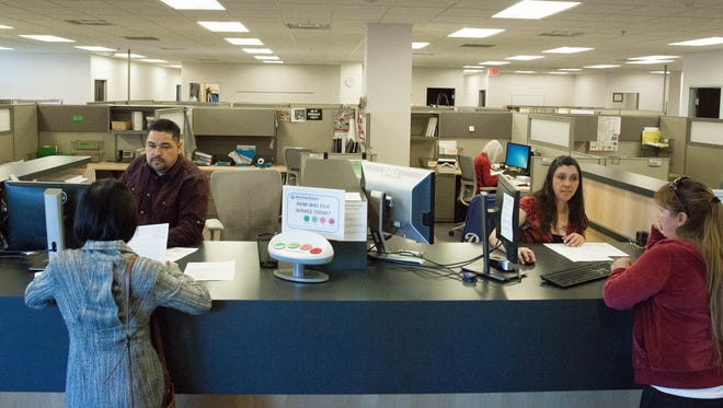 Ramon Moreno, left and Christina Abeyta, right, help customers take care of permitting issues in the City of Las Cruces Community Development Department at City Hall on Friday, Feb. 9, 2018. The Community Development department will shift to offering services 7 a.m. to 6 p.m. Monday through Thursday, and 7 to 11 a.m. on Fridays.