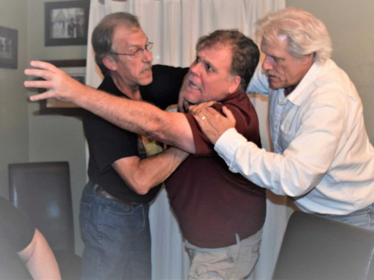 """Juror number 3 played by Mack Heath, loses control in the intense jury room of the play """"12 Angry Men."""" He's being restrained by fellow jurors played by Pau; Weir (left) and Bill Hit."""