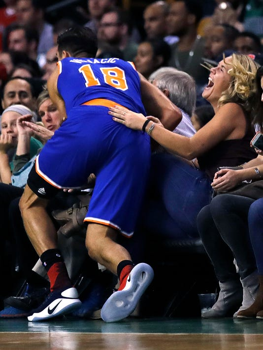 A woman seated in the front row laughs as New York Knicks guard Sasha Vujacic, of Slovenia, nearly lands in her lap during the first quarter of the Knicks' preseason NBA basketball game against the Boston Celtics in Boston, Wednesday, Oct. 19, 2016. (AP Photo/Charles Krupa)