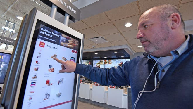 Jeff Monica demonstrates how to use the kiosks at the newly renovated McDonald's on Hanley Road earlier this year in this News Journal photo.