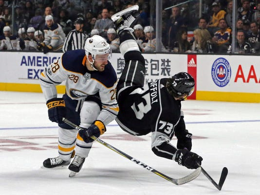 Buffalo Sabres center Zemgus Girgensons (28) and Los Angeles Kings center Tyler Toffoli (73) tangle during the second period of an NHL hockey game in Los Angeles on Saturday, Oct. 14, 2017. (AP Photo/Reed Saxon)