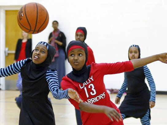 Amira Ali, right, and Rayan Ali, left, play basketball