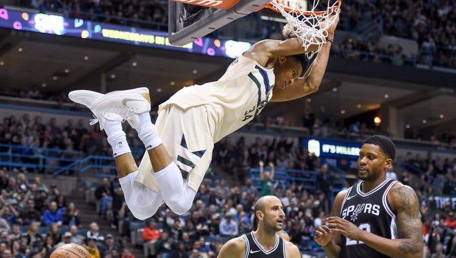 Bucks forward Giannis Antetokounmpo dunks  against Spurs guard Manu Ginobili (20) and forward Rudy Gay.