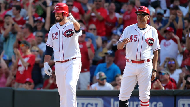 Cincinnati Reds pitcher Jackson Stephens (62) gestures toward Cincinnati Reds third base coach Billy Hatcher (22) after hitting a two-RBI single in the fourth inning during the National League baseball game between the Chicago Cubs and the Cincinnati Reds on July 1, 2017, at Great American Ball Park.