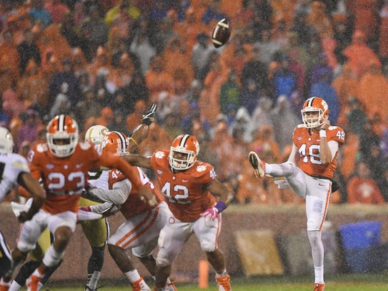 Clemson punter Will Spiers (48) punts against Georgia