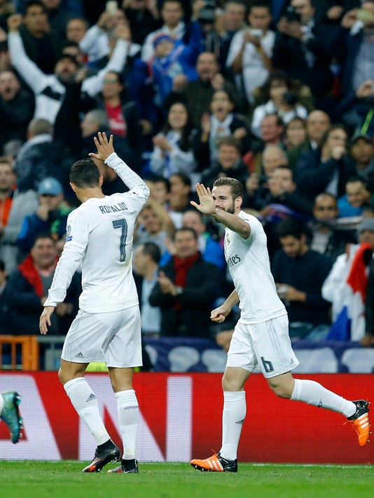 Real Madrid's Nacho Fernandez, right, celebrates with his teammate Cristiano Ronaldo after scoring the opening goal of his team during the Champions League group A soccer match between Real Madrid and PSG at the Santiago Bernabeu stadium in Madrid, Tuesday, Nov. 3, 2015. (AP Photo/Francisco Seco)