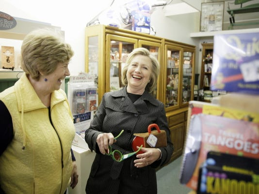 Democratic presidential candidate Hillary Rodham Clinton laughs with Laree Randall, owner of Laree's gift shop, as she looks at toys Tuesday, May 19, 2015, in Independence, Iowa.