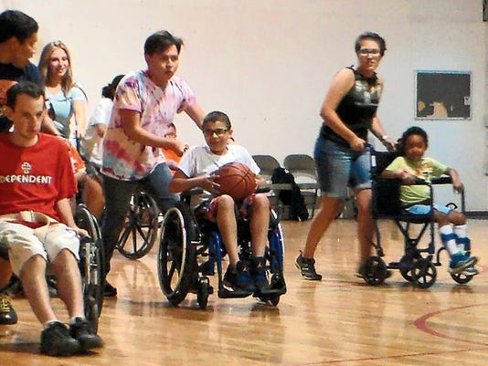 A wheelchair basketball team participates in the Muscular Dystrophy Association's 2014 summer camp mobile program.