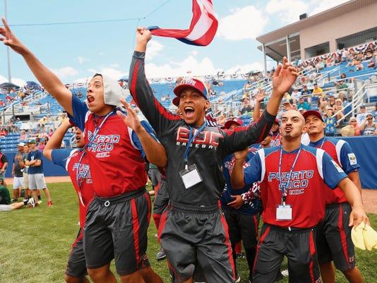 Members of La Escuela de los Deportes de Carolina cheer for their teammate, Alexander Martinez, in the Connie Mack World Series Home Run Derby on Sunday at Ricketts Park in Farmington.