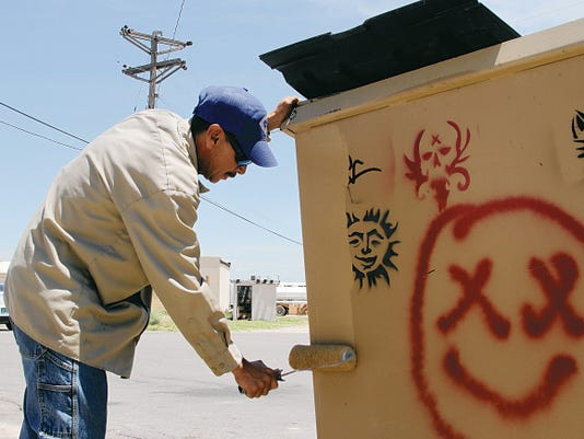 Felipe Villareal, the foreman for community service for the City of Carlsbad works to cover up graffiti found on a dumpster. Villareal said that he goes across the city multiple times a week to clean up the graffiti.