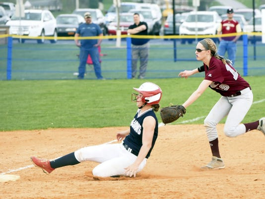 Chambersburg's Sam Bender (19) slides into third base ahead of a tag by shortstop Nicole Baker of Shippensburg on a fielder's choice play. The Trojans earned an 11-5 victory Friday at Norlo Park.