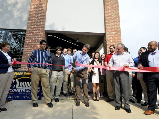 Sapio Sciences' CEO and founder Kevin Cramer, center, cuts the ribbon on Sept. 4 outside the company's new offices.