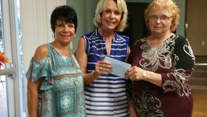 Whispering Sound Women's Club presents a donation to Caring Children Clothing Children (4CS). The money will help fund new shoes, socks and underwear and books for thelibrary. Pictured are, from left, Roseanne Donovan, with Whispering Sound, Judy Tenzyk of Caring Children Clothing Children, and Brenda Moran, also with Whispering Sound.