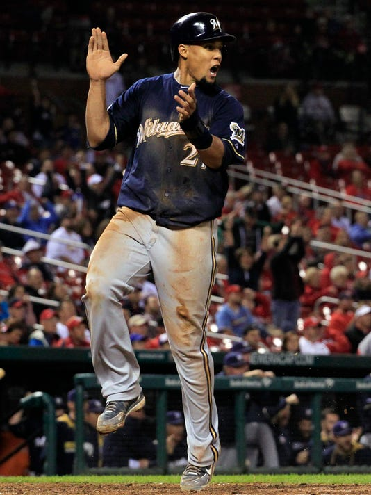 Milwaukee Brewers' Carlos Gomez applauds as he scores on single by Hector Gomez during the 12th inning of a baseball game against the St. Louis Cardinals Tuesday, Sept. 16, 2014, in St. Louis. (AP Photo/Jeff Roberson)