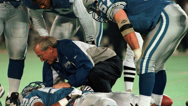 The Lions' Reggie Brown is attended by a trainer as Detroit's Antonio London (55) and Stephen Boyd (57) look on in the fourth quarter of their game against the New York Jets Sunday, Dec. 21, 1997, at the Silverdome in Pontiac.