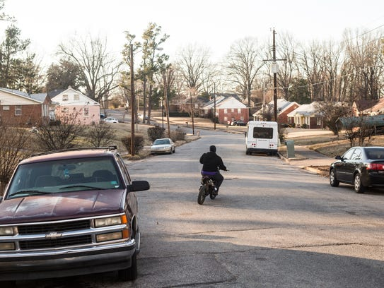 A young man rides a dirt bike on Wellons Avenue in