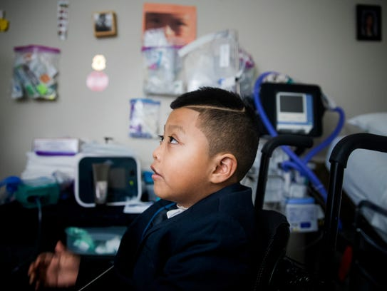 Ricky Solis, 6, waits in his wheelchair to drive to