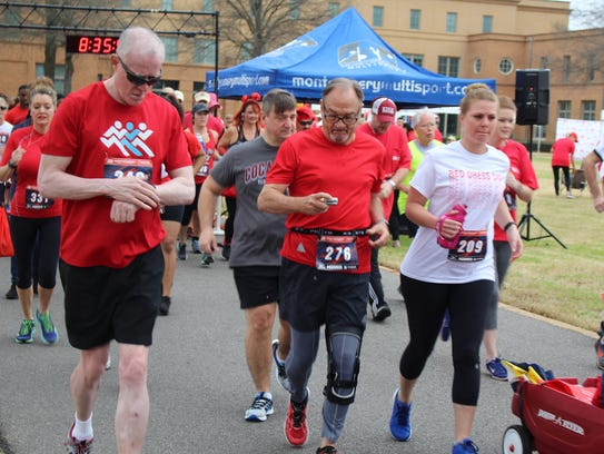 Runners check their times during Saturday's Red Dress