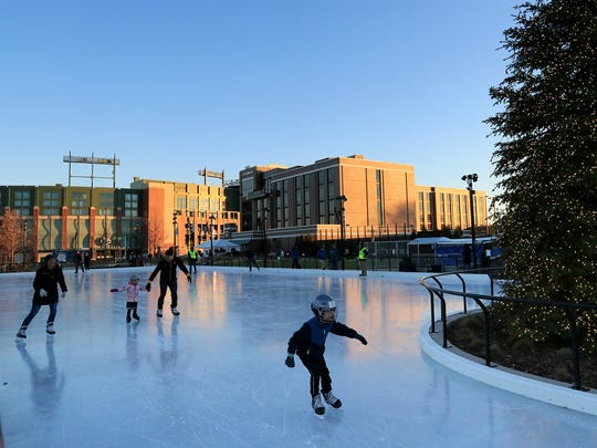 Anthony and Amanda Renkas of De Pere skate with their kids, Ben, 6, and Natalie, 4, after the ribbon-cutting ceremony for the ice skating pond at the park in Titletown on Thursday in Ashwaubenon.