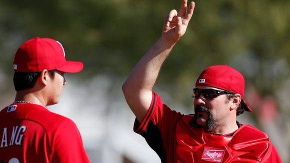 Reds catcher Corky Miller, right, talks with pitcher Chien-Ming Wang during practice at spring training in Goodyear in February.