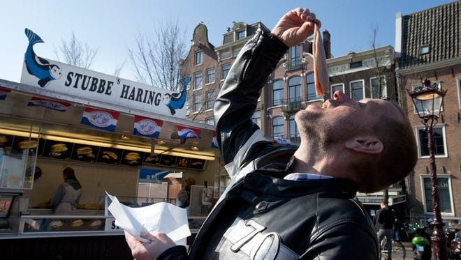 Associated Press reporter Mike Corder demonstrates how to eat raw herring outside one of Amsterdam's ubiquitous  herring stands on March 12, 2014.