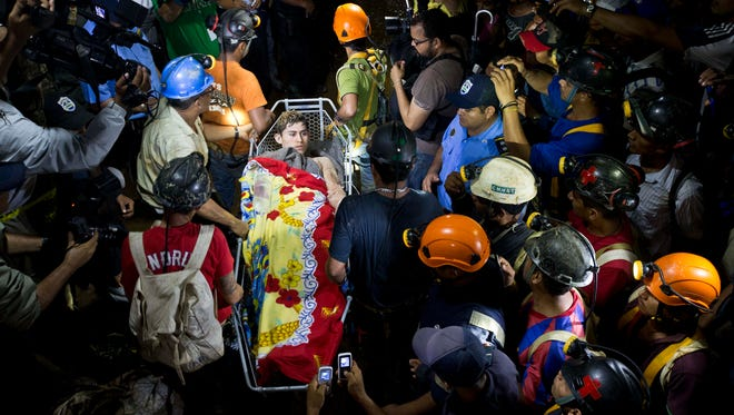 A rescue miner is carried away on a stretcher as he is evacuated from the El Comal gold and silver mine in Bonanza, Nicaragua, Friday, Aug. 29, 2014.  The first 11 of 24 freelance gold miners trapped by a collapse in this mine have been rescued and crews were working early Saturday to free more, officials said.