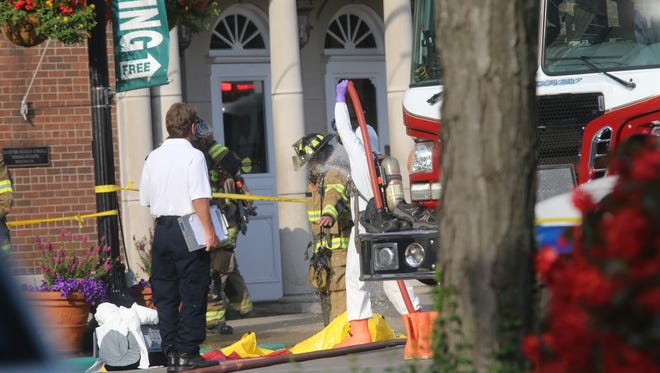 A Murfreesboro firefighter goes through a decontamination process after investigating a suspicious package at the Judicial Building on Public Square.