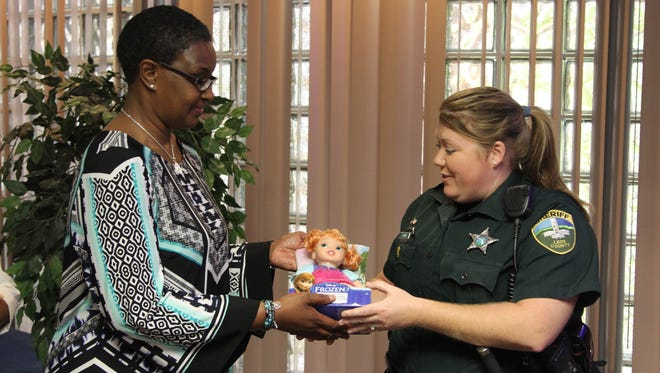 Sandra Collins, executive director of the I Heard Your Cry Foundation, gives a doll to a victim advocate with the Leon County Sheriff's Office.
