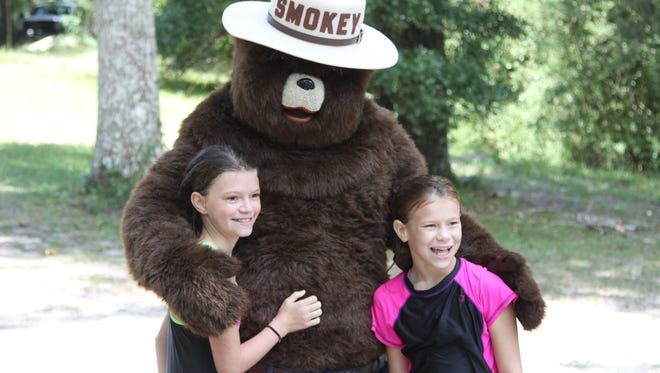 Smokey Bear greets two fans at Wakulla Springs State Park, where he celebrated his 70th birthday.