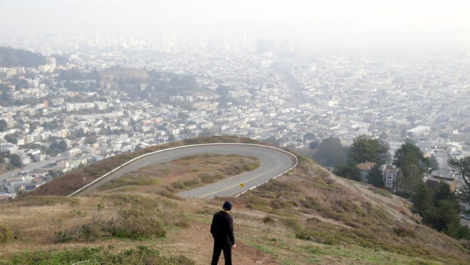 A visitor hikes down a pathway overlooking the skyline on Twin Peaks.